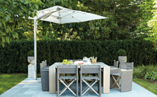 Natural materials lend this dining area an appealing simplictiy. The cantilevered shade is by Tuuci