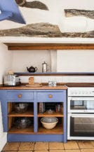 Painted units in the kitchen, produced by Landmark's skilled in-house furnishings team. Note the old stone showing through the plaster.