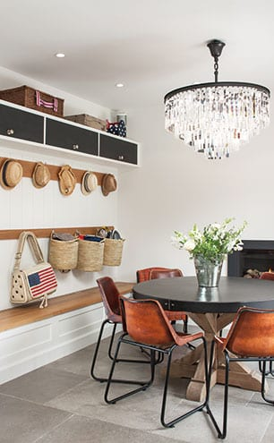 The circular table is surrounded by leather dining chairs from Rockett St George in the boot room area of the kitchen, with personalised storage and hooks