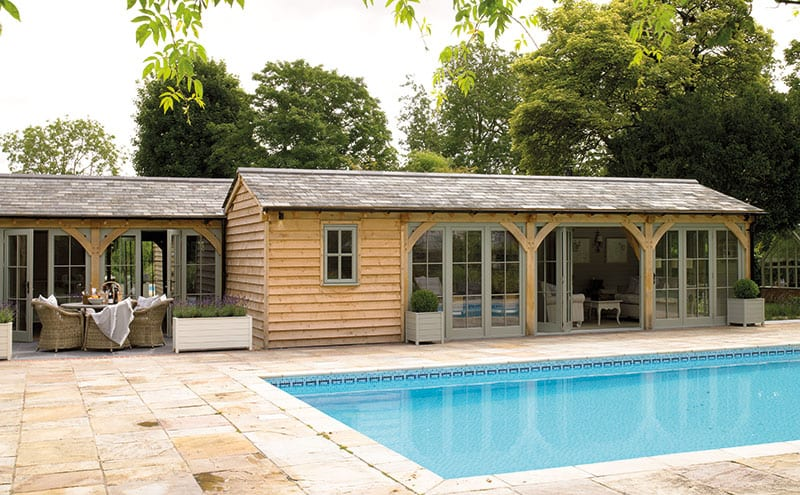 The roof is clad in black Welsh slate that complements the warmth of the slatted oak façade. Farrow & Ball's Pigeon 25 adds some subtle colour to the structure