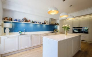 the island unit helps to define each zone while keeping the area fluid and open-plan. A painted glass splashback adds a bright pop of colour to the muted palette
