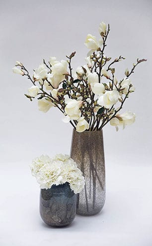 Bloomed and Budding white magnolia stems in bubble glass vase, from £395; white hydrangeas in duo tone thick glass vase, from £195, Lifelike Flowers.