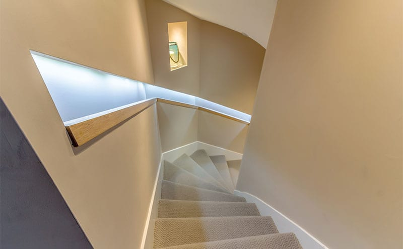 The stairway leading to the open-plan kitchen and dining area in the extension, its integrated lighting highlighting the minimal wooden banister