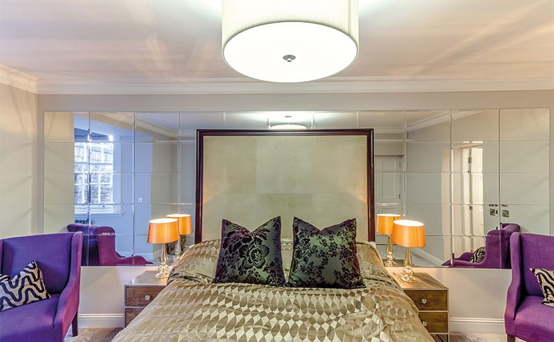 A sumptuous bright bedroom, its mirrored wall panelling reflecting light and space