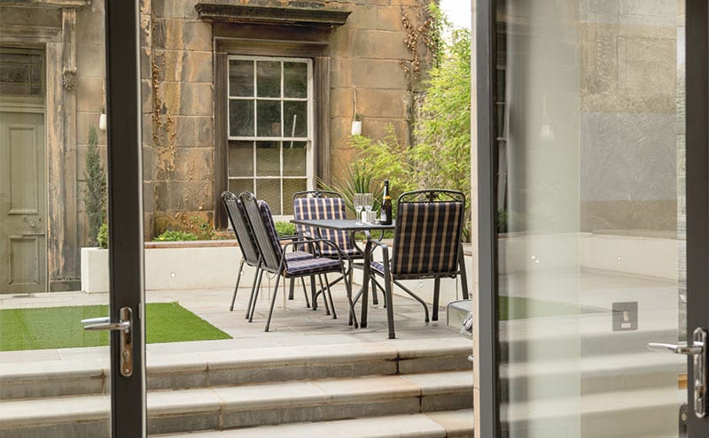 Pale sandstone slabs help the garden to feel light and bright, while the artificial lawn keeps maintenance to a minimum