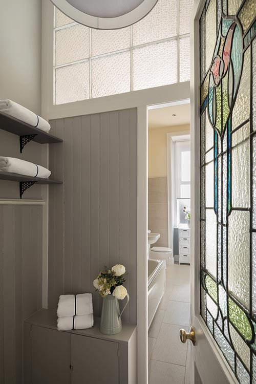 Simplicity rules in the bathroom, where a largely pale and neutral palette of colours and materials allows period details such as tongue-and-groove panelling and the stained-glass door to shine