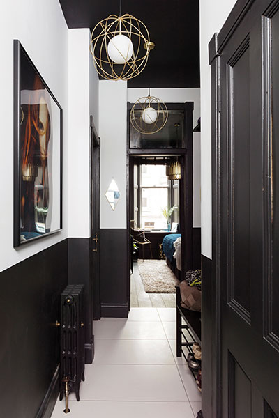 the brass and black combination extends the hall, where the upper portion of each wall has been painted white to bring brightness into the central part of the house