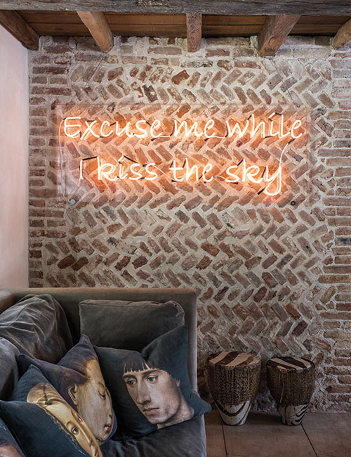 McNeill enjoys juxtaposing old and new. Here, medieval herringbone pattern brickwork is visible behind a Perspex panel which displays a neon quote from Jimmy Hendrix's 'Purple Haze'. The portrait cushions on the sofa were printed for McNeill by Digitex