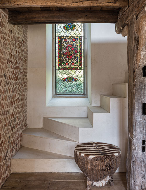 The simple helical staircase, built of Spanish limestone, was designed by McNeill. Fragments of medieval stained glass were set into the tall leaded window, made by Bronze Casements