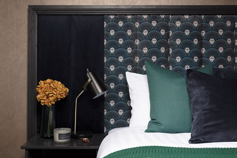The guest bedroom follows the boudoir theme, mixing velvets with bold pattern