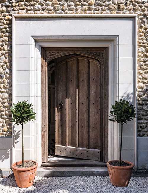 The front door is framed by a limestone surround reclaimed from a ruined 15th-century monastery