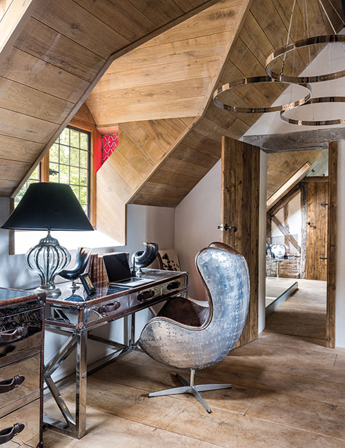 A work area is incorporated into the spacious main bedroom. The chrome desk and Aviation armchair are both from Andrew Martin. The internal doors throughout the house were made using reclaimed Scandinavian pine scaffold boards