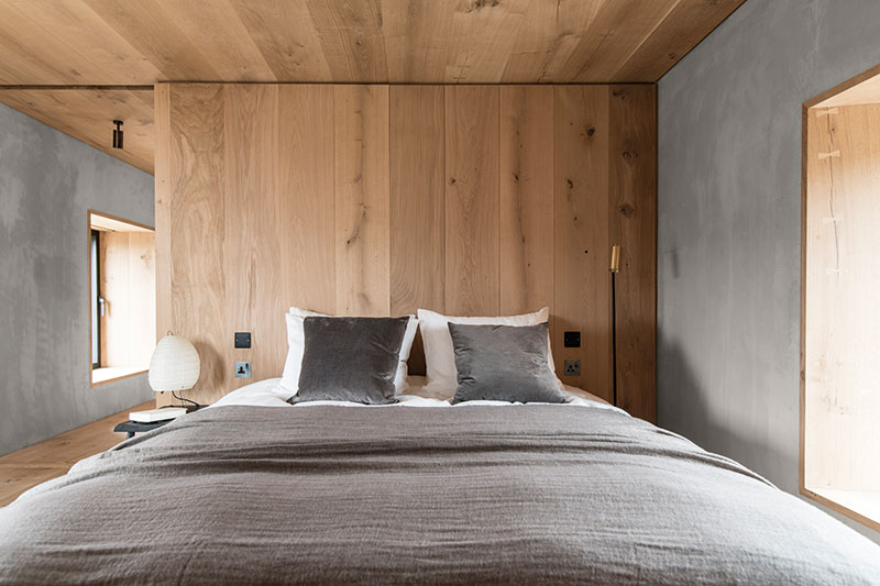 The bedroom is a stripped-back affair, with a bespoke bed built to fit the space