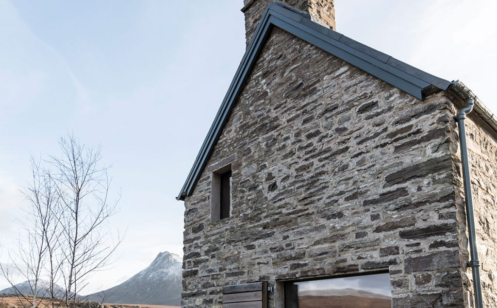 The gable shows the exterior's reclaimed stone, as well as the new window openings