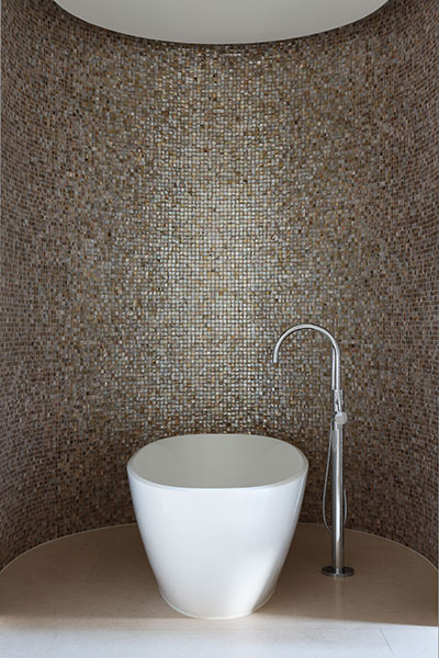 This guestroom en-suite shimmers in lustrous mosaic tiles. The freestanding bath is by Duravit