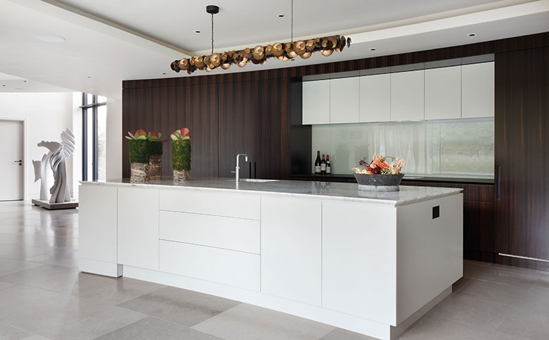 Subtle curves in the Artichoke kitchen can be seen in the marble-topped island and the concealed doors that lead to the scullery