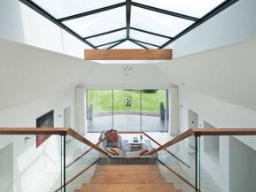 A timber-clad steel tie was necessary to hold the frame of the extension together. The sofa at the foot of the stairs is by John Sankey, while the coffee table, built from an old engine, is by Vee8Design. Booths of Inverurie installed the Lutron lighting system and the Occhio lights