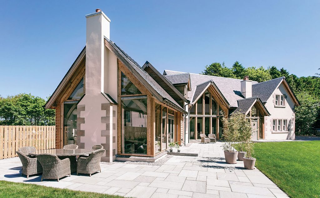 The house consists of two wings and a turret, with an exterior finish of larch cladding, stone and white K-Rend render