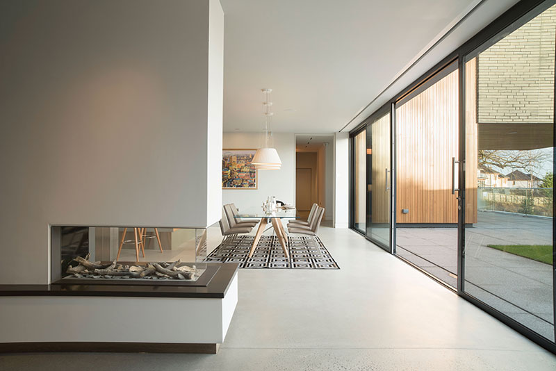 The external timber cladding by Russwood glows in the afternoon sun, its natural warmth linking the house to its garden and broader surroundings. IDSystems' six-panel set of doors slides open completely, allowing inside and out to become one