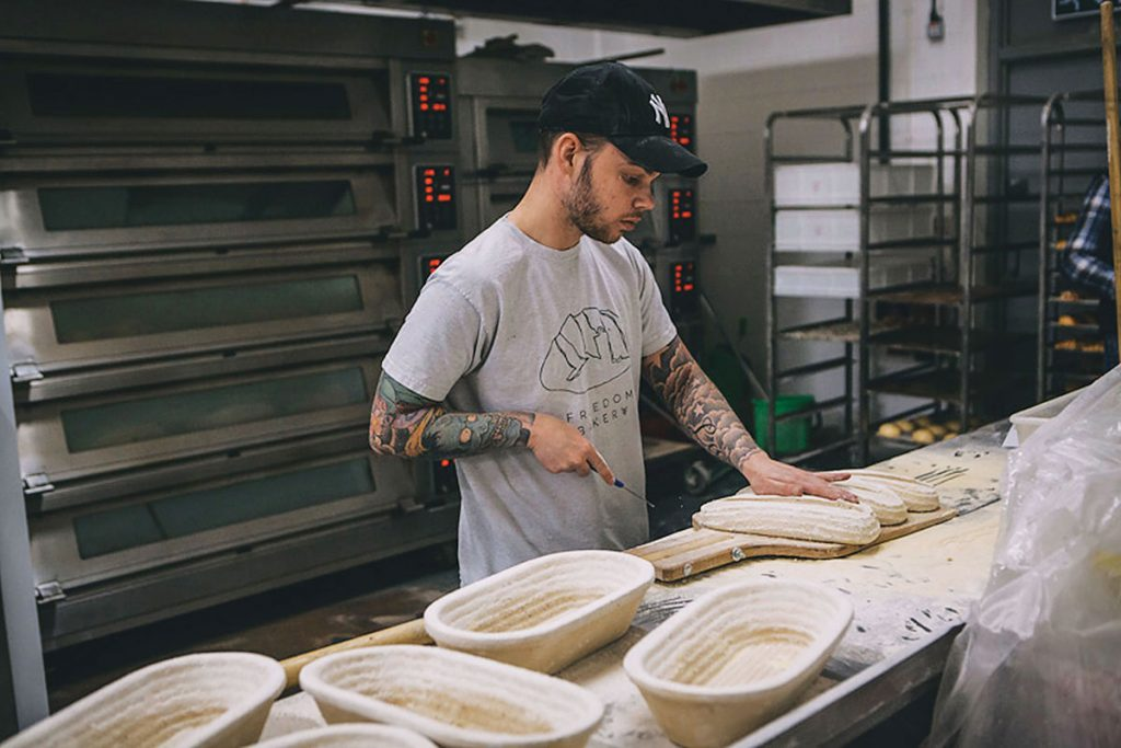 Lee-MacAloney,-one-of-the-Freedom-bakers,-scoring-sourdoughs-to-go-into-the-oven