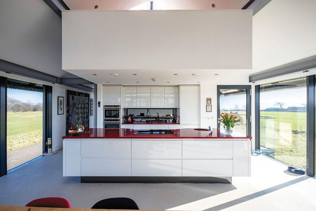 open-plan-white-kitchen-with-red-worktop