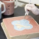 a-fine-brush-is-used-to-fill-different-coloured-liquid-slips-into-an-encaustic-tile