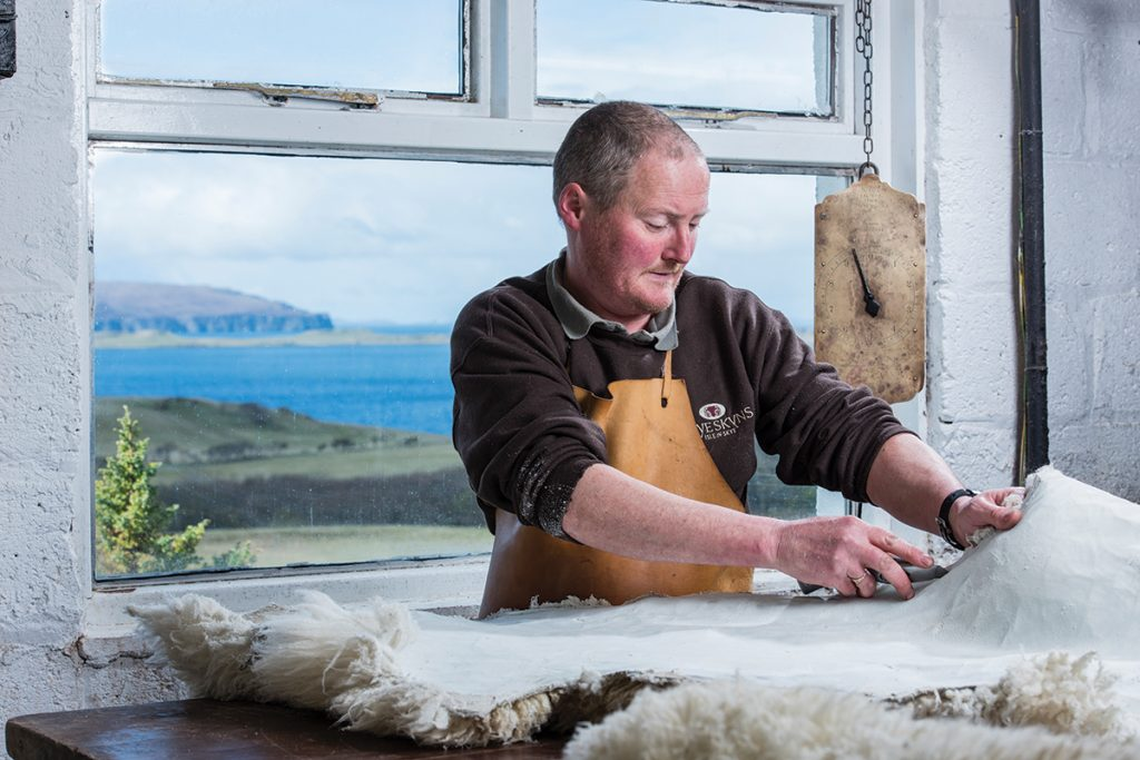Pete-trims-the-sheepskin-with-a-sharp-blade