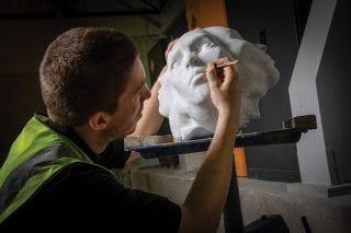 man-restoring-a-stone-head