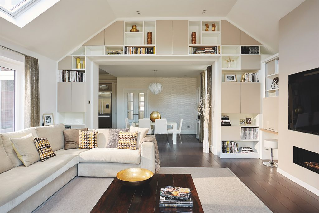 Bright white living room with large square open archway with built-in storage surround the opening