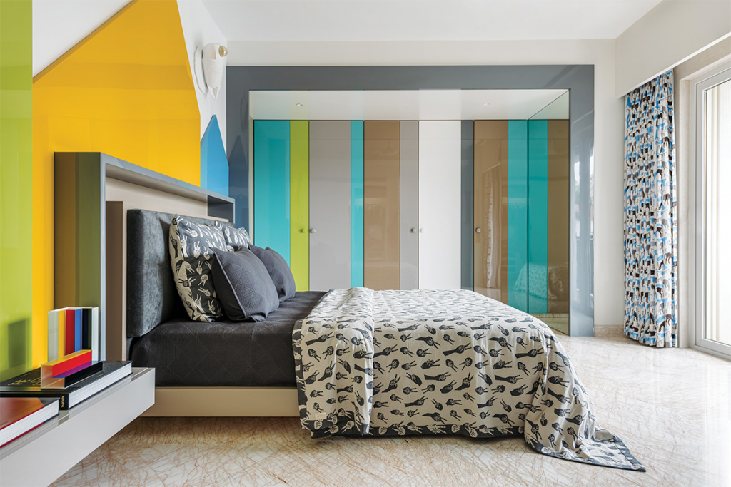 bold interior, blue cladding on the wall and a graphic bedspread on the right hand bed