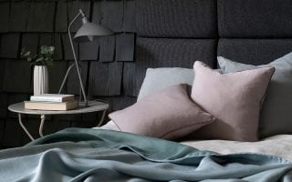 cosy bedroom set up with black walls and pastel blue and pink bedding from Marvic Textiles