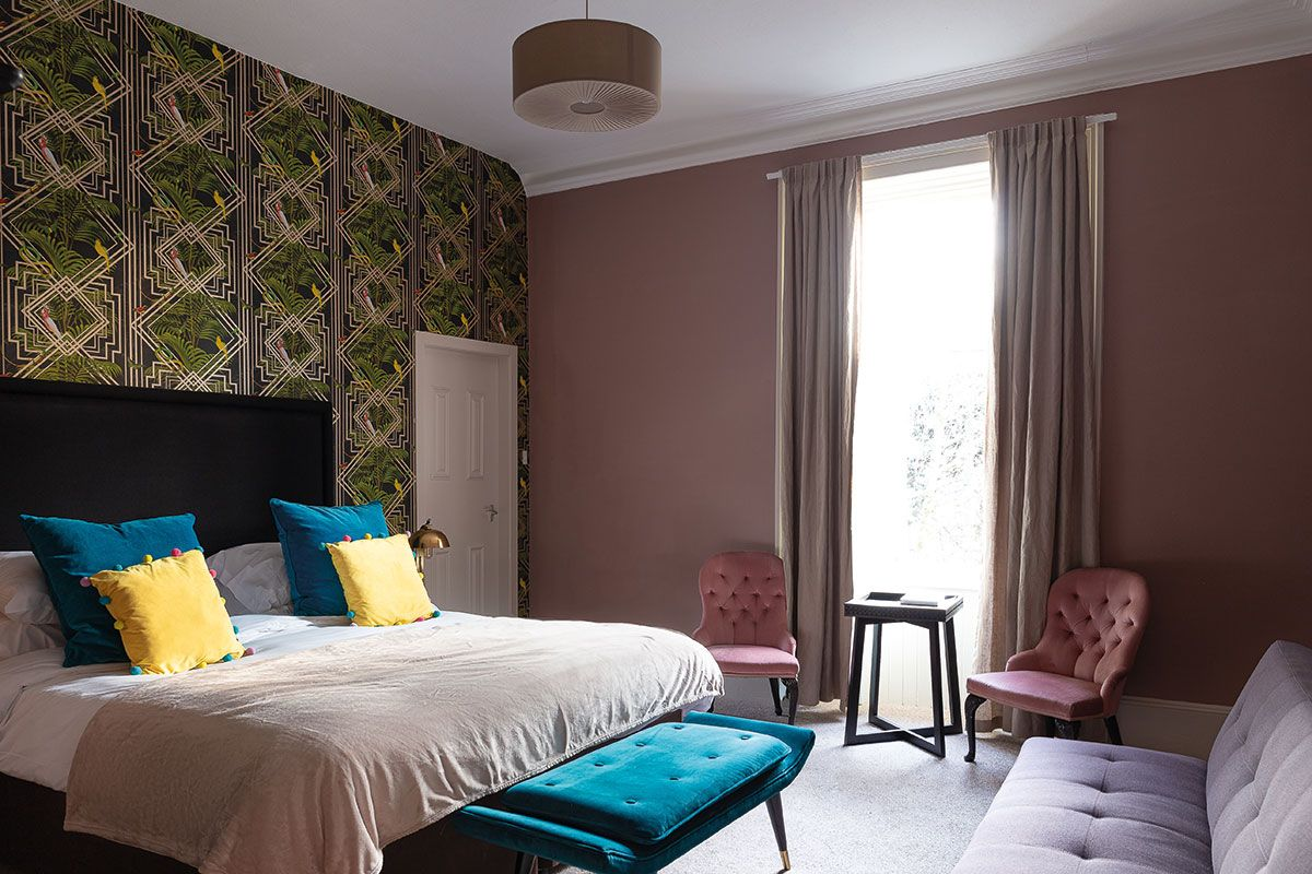 Saorsa-hotel-pink-room-with-blue-cushions-on-bed.jpg